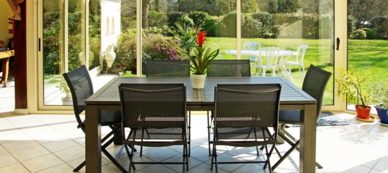 sunny conservatory with dark 6 seater dining table